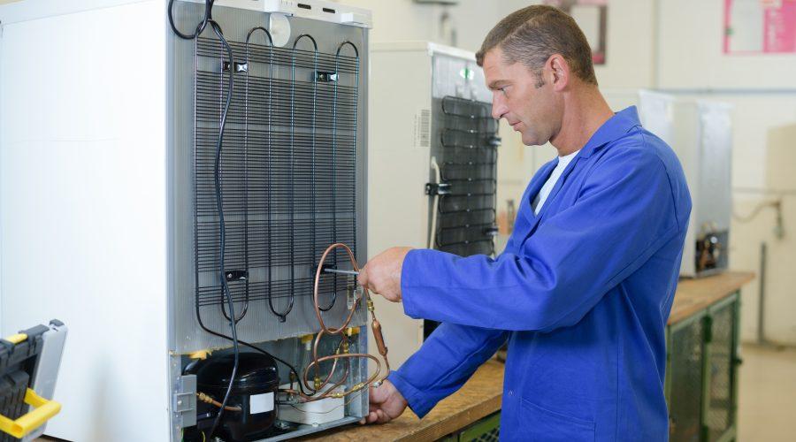 Rückseite eines Kühlschrankes wird von einem Mann repariert