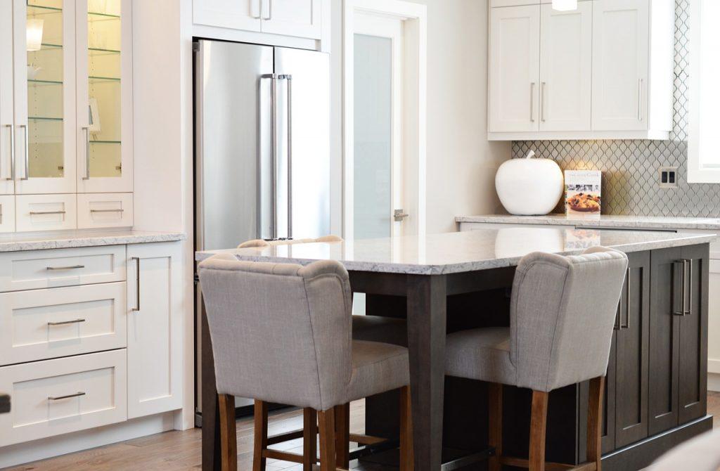 Küche mit einem Tisch und Stühlen in der Mitte.